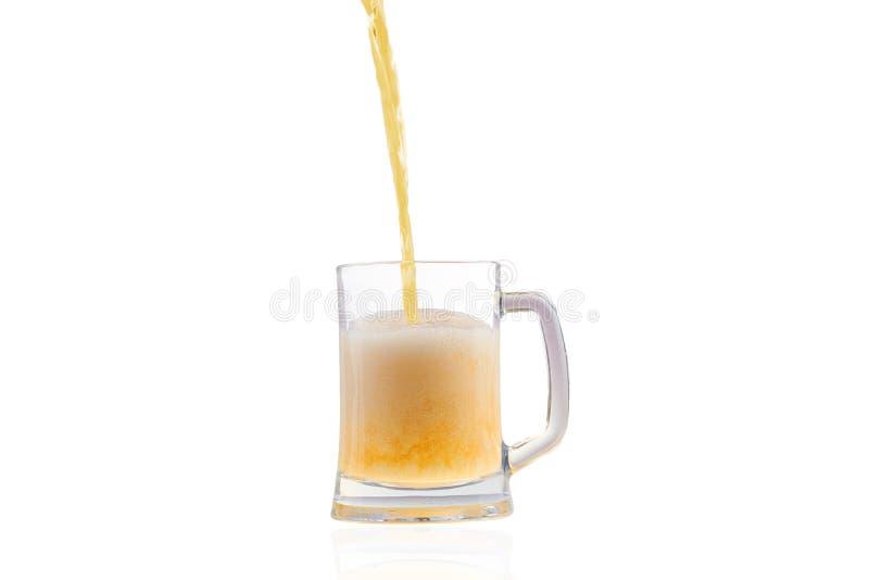 Пиво лить в наполовину полное стекло над белой предпосылкой стоковая фотография