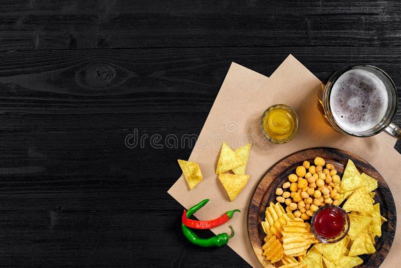 Пиво и закуски лагера на черном деревянном столе Гайки, обломоки Взгляд сверху с Copyspace стоковое фото