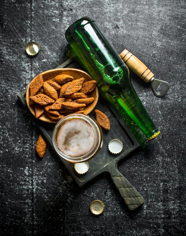 Пиво и мякиши на черной разделочной доске стоковое изображение rf