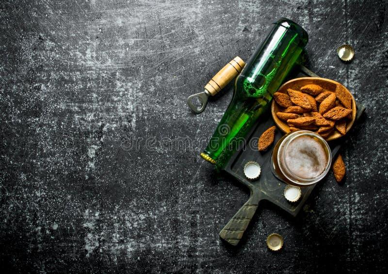 Пиво и мякиши на черной разделочной доске стоковое изображение