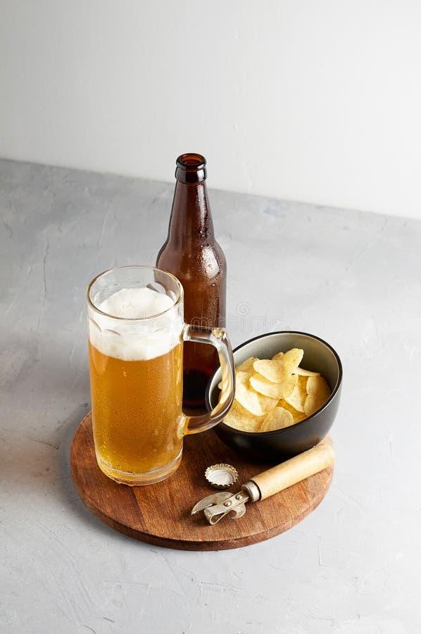 Пиво лагера в стекле и бутылке с картофельными чипсами стоковая фотография rf