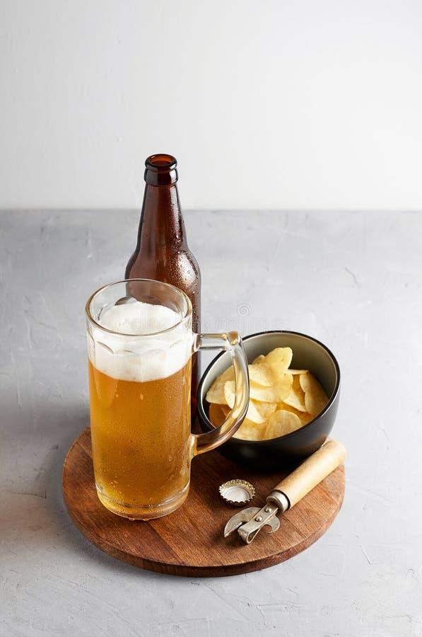 Пиво лагера в стекле и бутылке с картофельными чипсами стоковая фотография