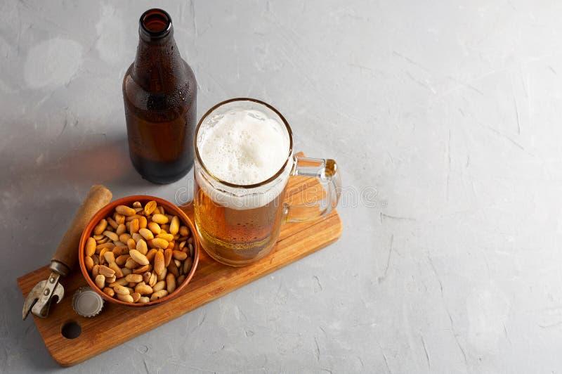 Пиво лагера лить в стекле и бутылке с посоленными арахисами стоковые фото