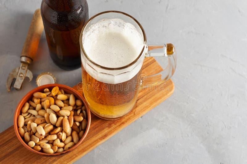 Пиво лагера лить в стекле и бутылке с посоленными арахисами стоковая фотография