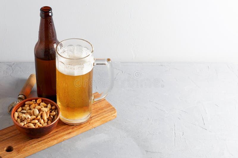 Пиво лагера лить в стекле и бутылке с посоленными арахисами стоковые изображения rf