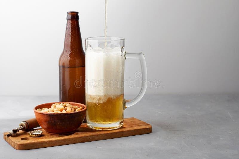 Пиво лагера лить в стекле и бутылке с посоленными арахисами стоковые изображения