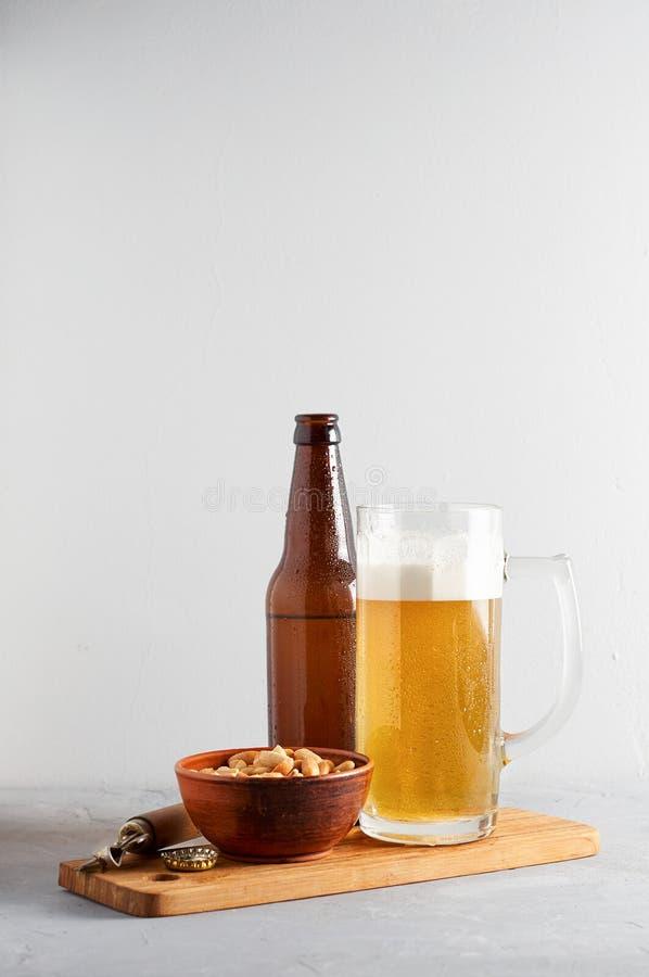 Пиво лагера лить в стекле и бутылке с посоленными арахисами стоковая фотография rf