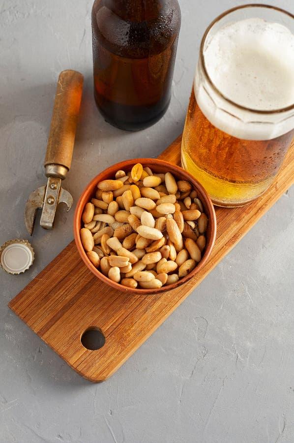 Пиво лагера лить в стекле и бутылке с посоленными арахисами стоковые фотографии rf