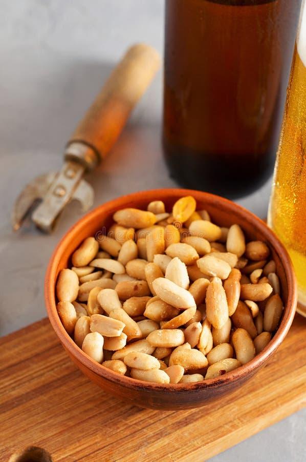 Пиво лагера лить в стекле и бутылке с посоленными арахисами стоковое фото