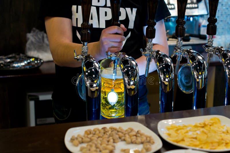Пиво проекта сервировки бармена в пабе стоковые фотографии rf