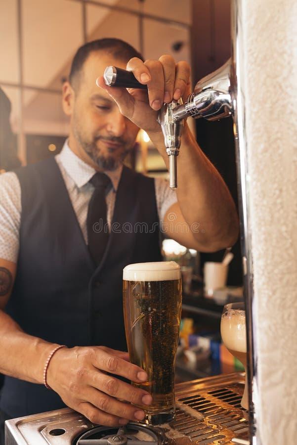 Пиво сервировки бармена в пабе стоковые фотографии rf