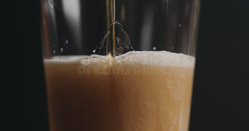 Пиво эля крупного плана лить в стекле над черной предпосылкой стоковые изображения