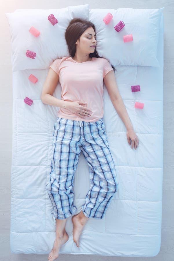 Пижамы молодой дамы нося спать с curlers волос в кровати стоковые изображения rf