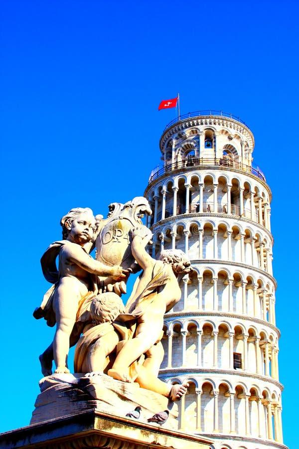 ПИЗА, ИТАЛИЯ - ОКОЛО ФЕВРАЛЬ 2018: Фонтан с ангелами и полагаясь башня Пизы на квадрате чудес стоковая фотография