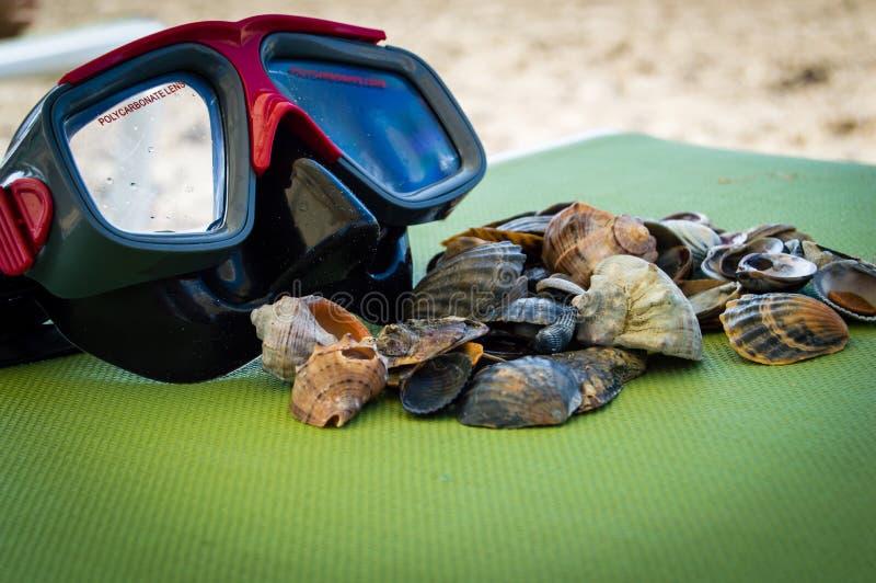 Пикирование акваланга маски с раковинами моря на предпосылке голубого зеленого цвета морского побережья стоковая фотография