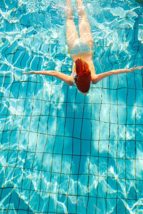 Пикирование девушки Redhead в бассейне снятом сверху стоковое фото rf