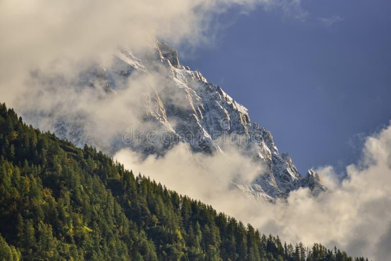Пики горной цепи Aiguilles и зеленый лес через облака chamonix Франция стоковая фотография