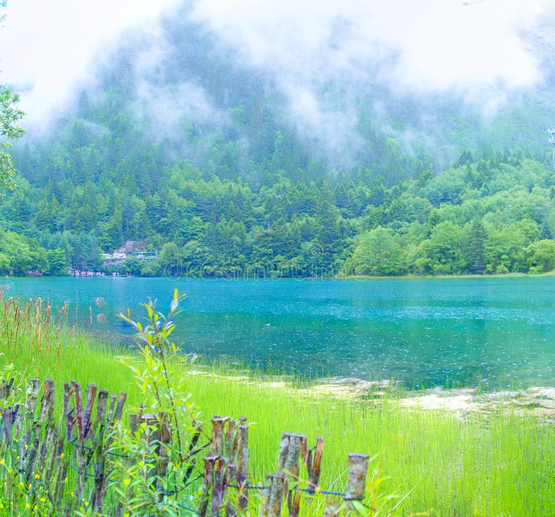 Пики и озера jiuzhaigou, пики в пределах живописной местности jiuzhaigou, между облаками и облаками Голубое озеро стоковые фото
