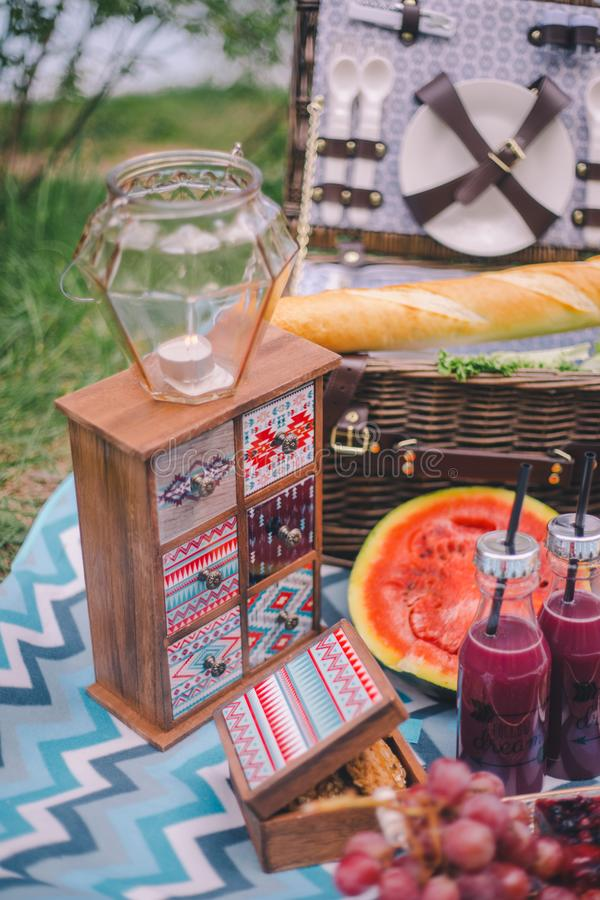 Пикник конца-вверх в природе Свеча в подсвечнике стоит на небольшом дрессере, рядом с ей лежит еда - арбуз, печенья виноградины, стоковое изображение