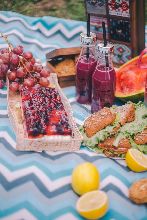 Пикник конца-вверх в природе Сэндвичи, торт, thermos, напитки и виноградины стоковое фото rf