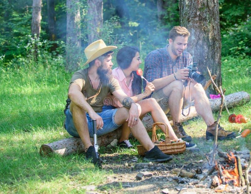 Пикник лета Hikers туристов ослабляя пока имеющ закуску пикника Пикник с друзьями в лесе около костра hikers стоковая фотография