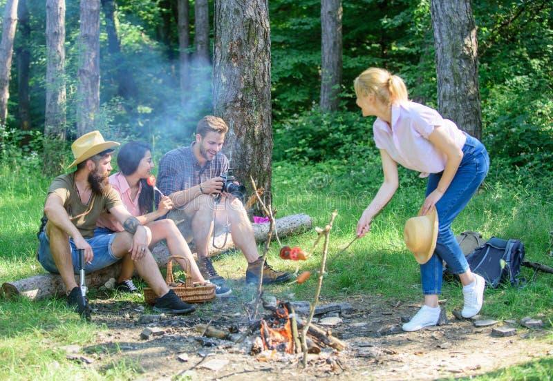 Пикник лета Hikers туристов сидят на закуске пикника журнала расслабляющей ждать Пикник с друзьями в лесе около костра стоковая фотография rf