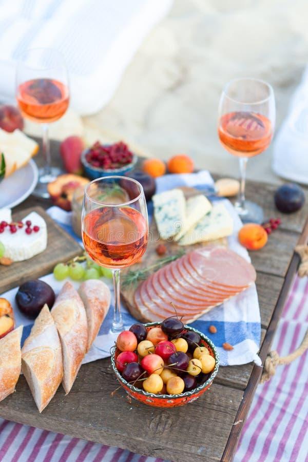 Пикник на пляже на заходе солнца в стиле зачатия boho, еды и напитка стоковое фото