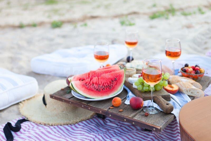 Пикник на пляже на заходе солнца в стиле зачатия boho, еды и напитка стоковые изображения rf