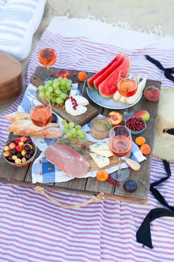 Пикник на пляже на заходе солнца в стиле зачатия boho, еды и напитка стоковые фото