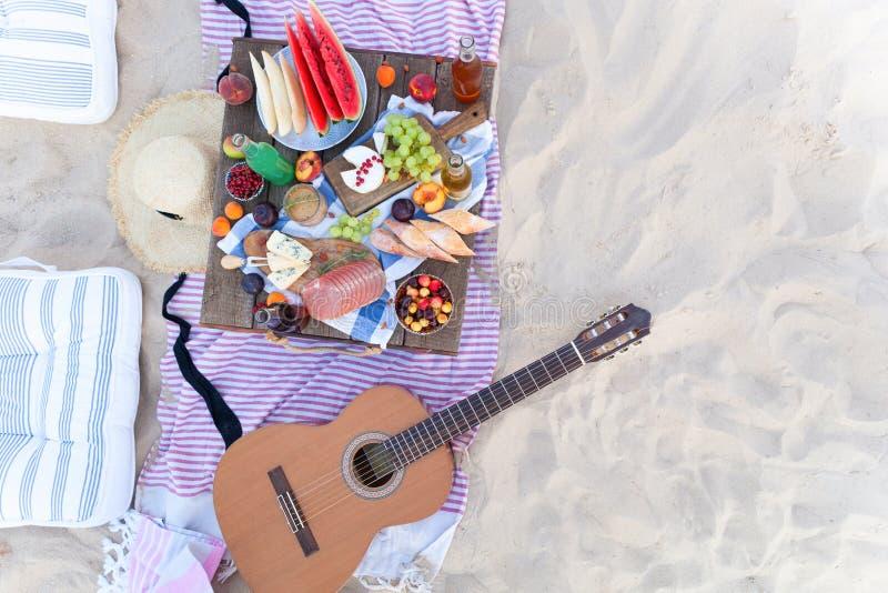 Пикник на пляже на заходе солнца в boho стиля, еде и зачатии напитка стоковые изображения