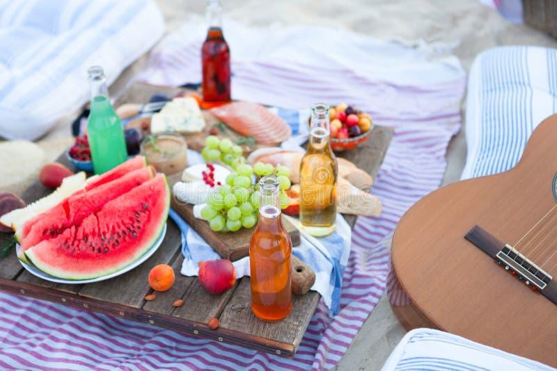Пикник на пляже на заходе солнца в boho стиля, еде и зачатии напитка стоковая фотография rf