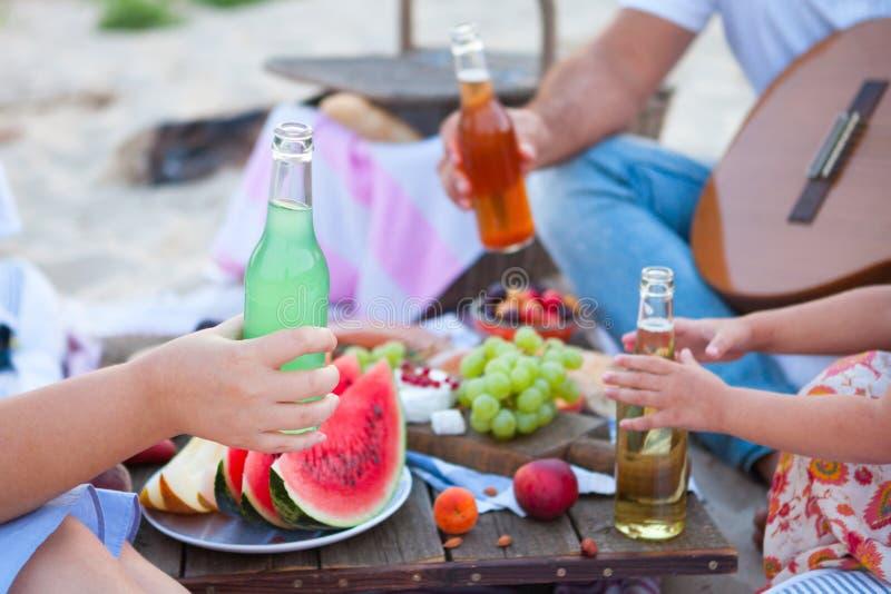 Пикник на пляже на заходе солнца в boho стиля, еде и зачатии напитка стоковые изображения rf