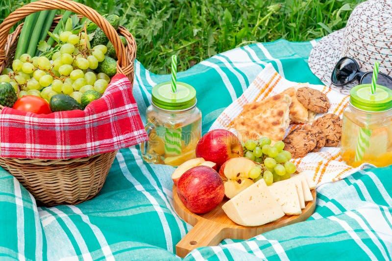 Пикник на траве на летний день - корзине, виноградинах, сыре, хлебе, яблоках - концепция воссоздания лета на открытом воздухе стоковое фото rf
