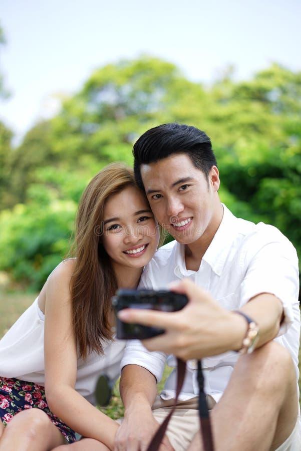 Пикник счастливых пар датировка внешний с камерой стоковое изображение rf