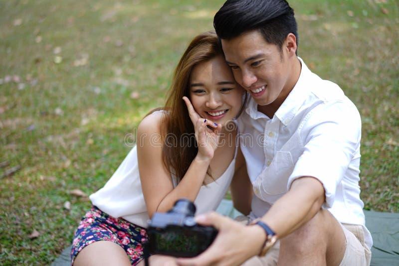 Пикник счастливых пар датировка внешний с камерой стоковая фотография rf