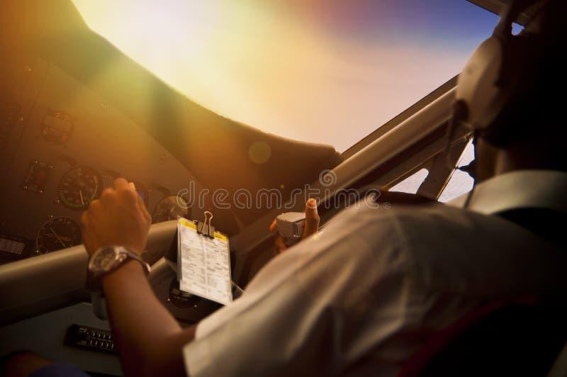 Пилот летая самолет пропеллера во время захода солнца стоковая фотография rf