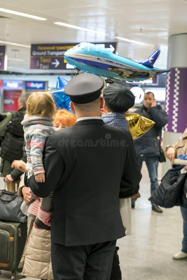 Пилот с его семьей на авиапорте Ребенок в руках Папы стоковое изображение rf
