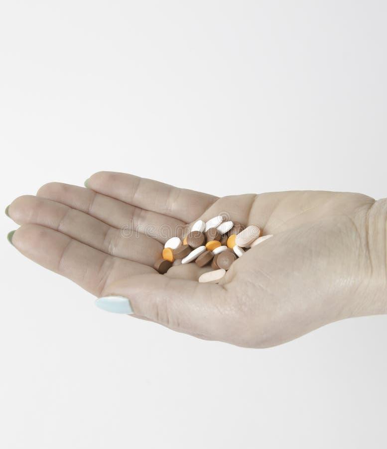 Пилюльки и лекарства разливают на руке lady's на белом backgrou стоковые изображения