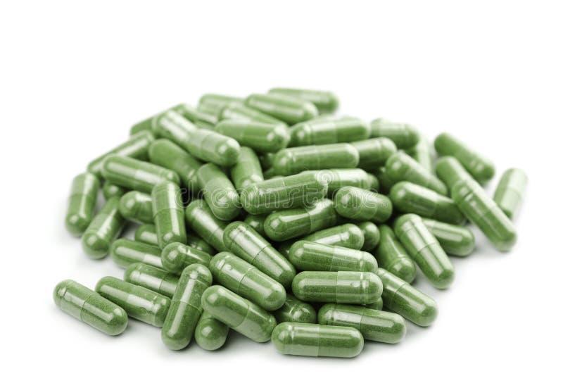 пилюльки капсулы изолированные зеленым цветом стоковая фотография