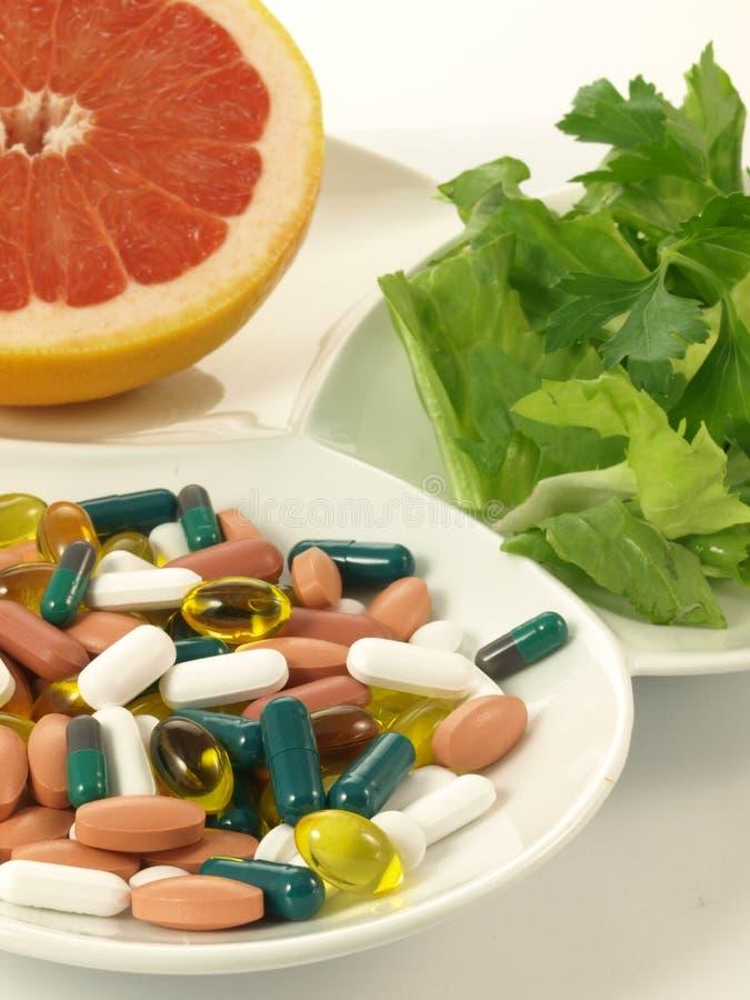 Пилюльки против витаминов, изолированного крупного плана, стоковые изображения