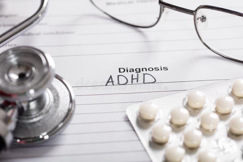 Пилюльки; Стекла и стетоскоп с диагнозом ADHD текста стоковые фотографии rf