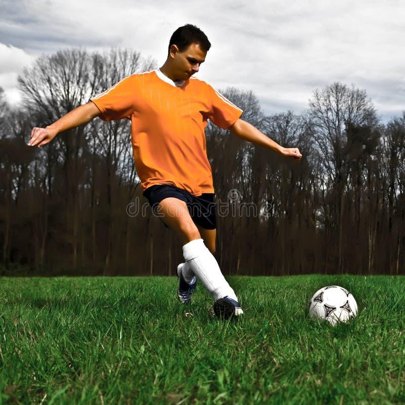пинать футбол игрока стоковая фотография rf