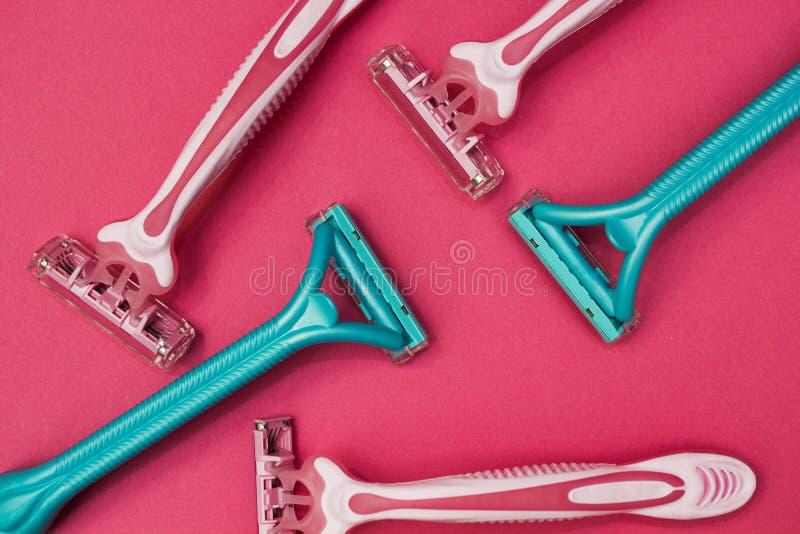 Пинк и голубые бритвы для женщин на розовой предпосылке стоковое фото