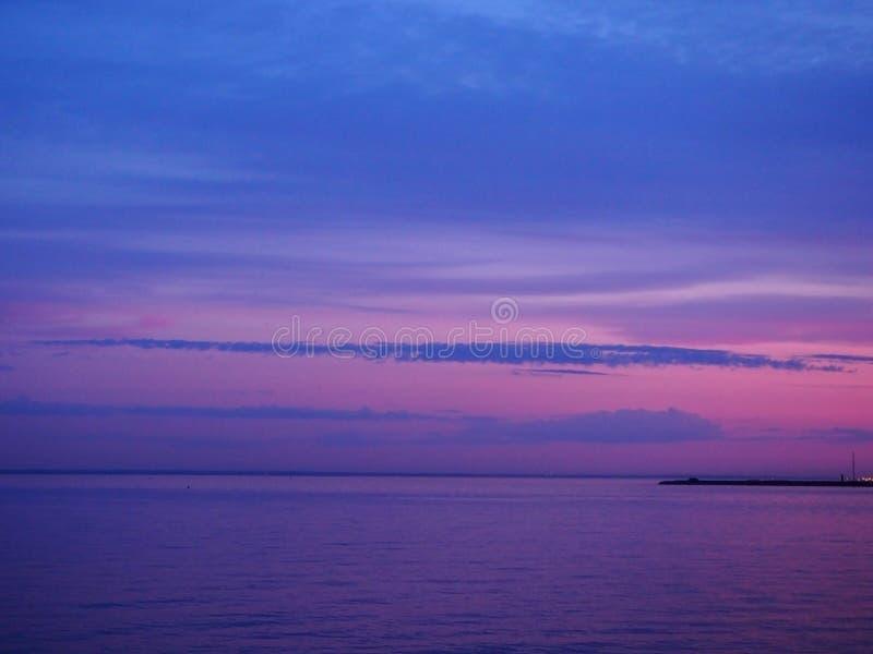 Пинк сумерек пестротканый и голубое небо на заходе солнца с красочным отражением в морской воде Панорамный морской ландшафт на th стоковое изображение