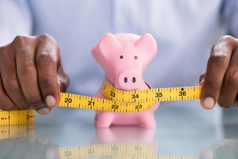 Пинк Piggybank человека измеряя с лентой измерения стоковые фотографии rf