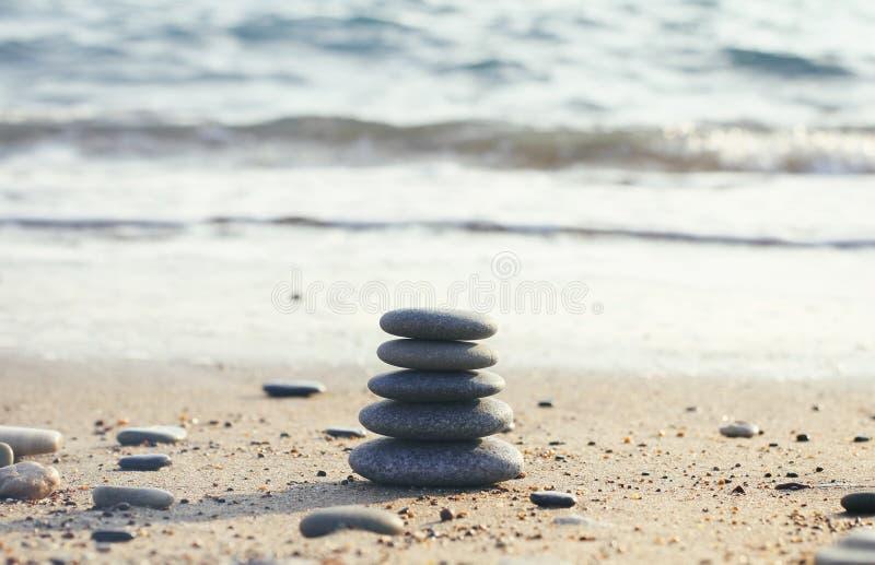 Пирамида дзэна камней спа на запачканной предпосылке моря Песок на пляже Берега моря Текстура волн воды Левая сторона фото Pla стоковое фото