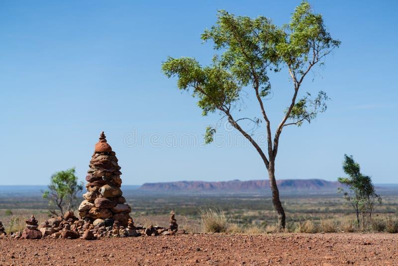 Пирамида из камней и эвкалипт с ландшафтом захолустья в предпосылке в NT Австралии стоковое изображение rf