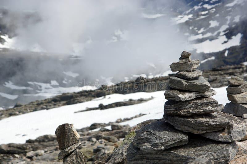 Пирамида из камней поверх горы со снегом и туманом стоковое фото
