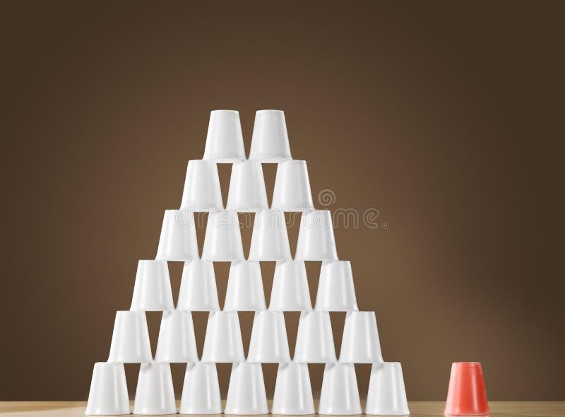 Пирамида белых пластичных чашек на таблице рядом с одиночной красной чашкой стоковые фотографии rf