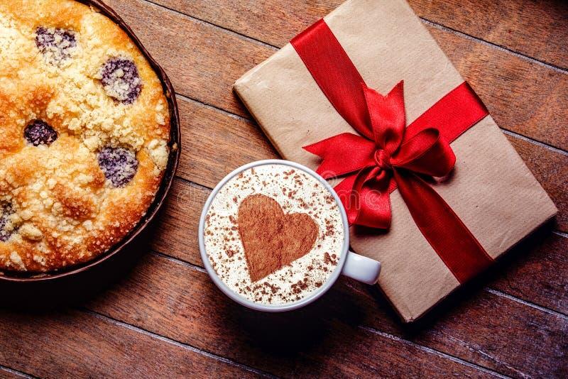 Пирог и чашка кофе с сердцем формируют с подарочными коробками стоковая фотография